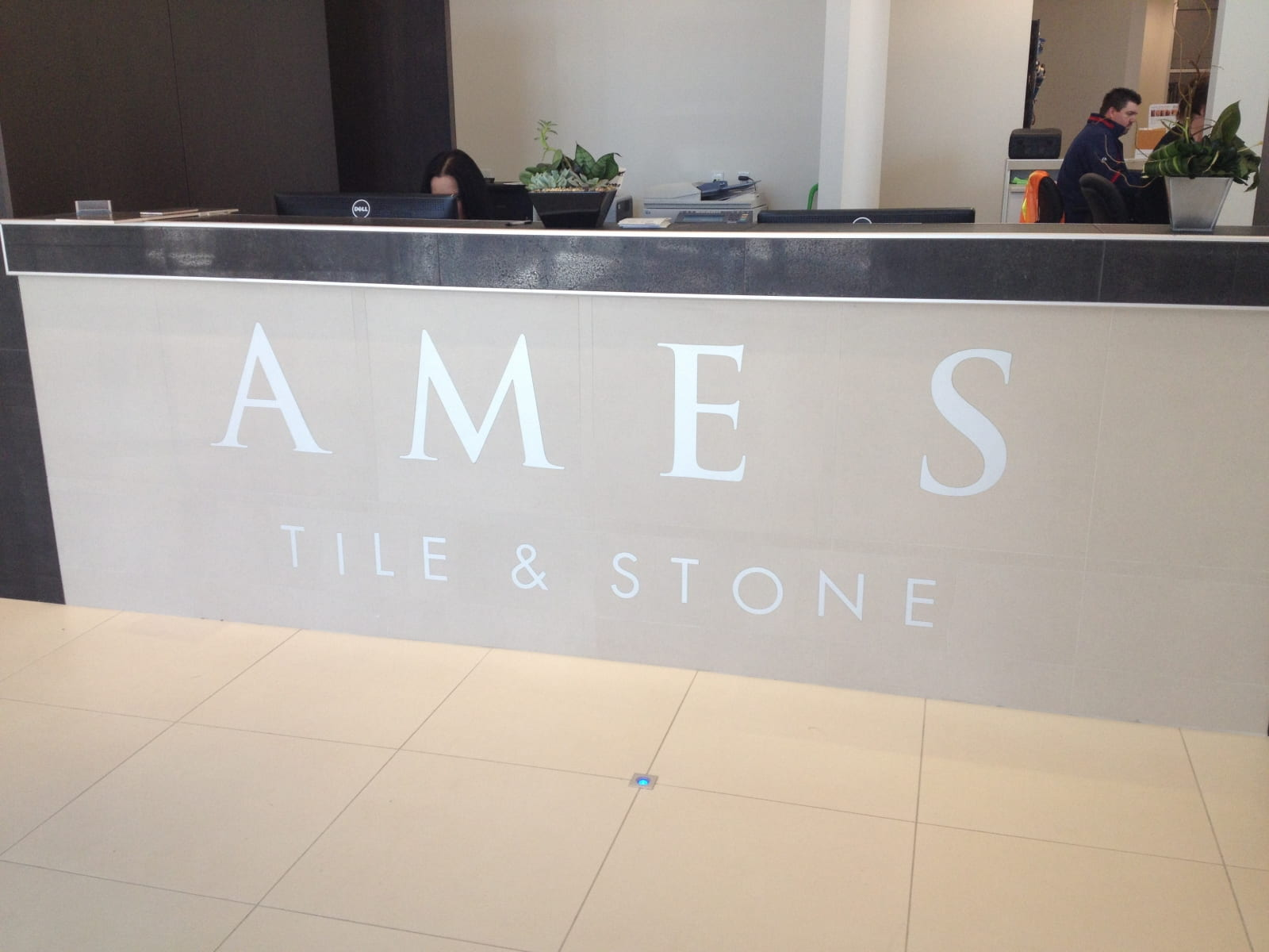 Vivid House Number | Custom Commercial Sign | AMES Tile & Stone | White Finish in front of a beige reception desk